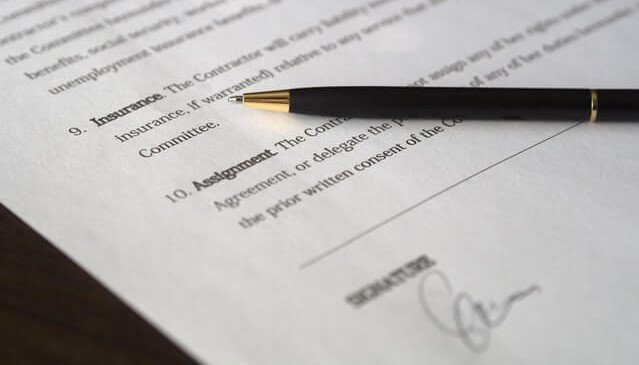 Signed Contract on table with Pen Finding the Best Trucking Insurance