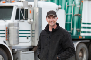 Man standing in front of white semi truck with green stripes