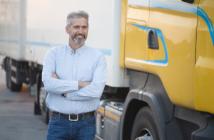 Truck Driver standing in front of yellow semi tractor trailer